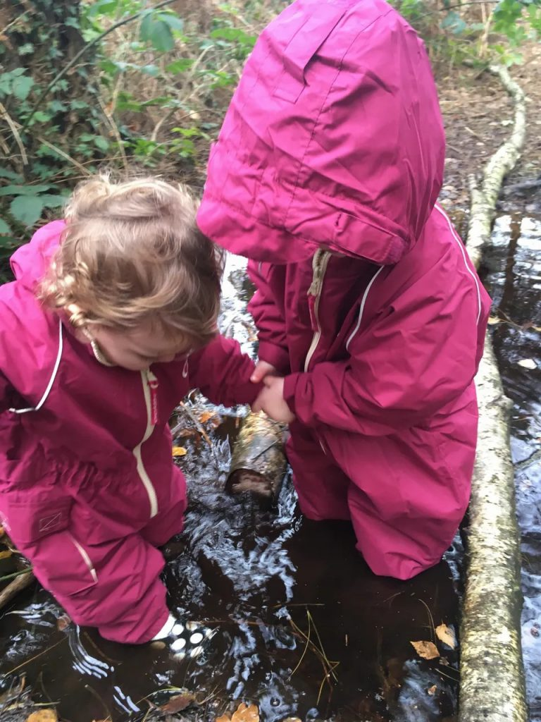 2 girls in pink waterproofs playing in puddles